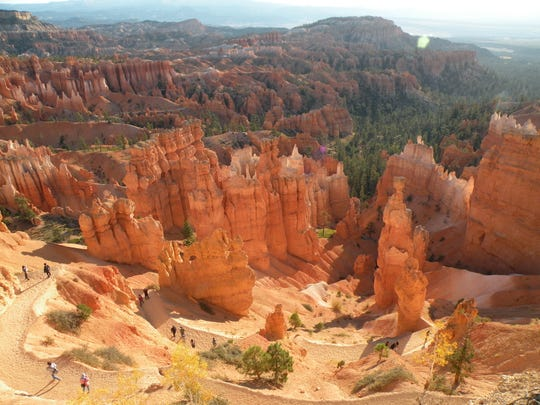 Hikers walk along the Queens Garden Trail in Bryce Canyon National Park. The park is famed for its many brightly colored hoodoos, tall spires made of sedimentary rock.