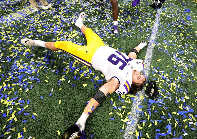 Dec 7, 2019; Atlanta, GA, USA; LSU Tigers offensive lineman Austin Deculus (76) does a snow angel in confetti after their win against the Georgia Bulldogs in the 2019 SEC Championship Game at Mercedes-Benz Stadium. Mandatory Credit: Jason Getz-USA TODAY Sports