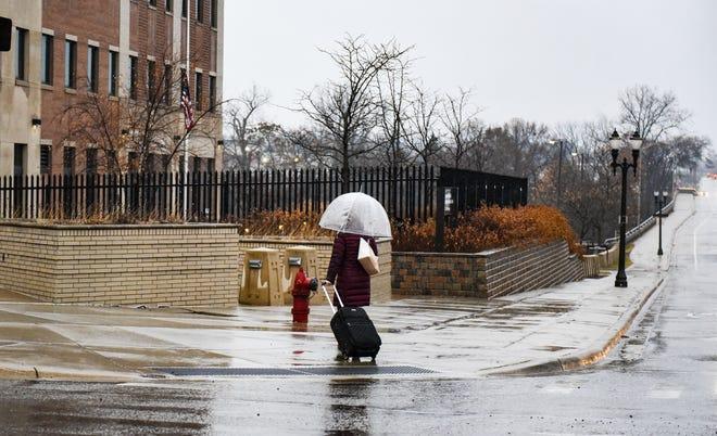A woman walks in the rain Monday morning, Dec. 9, 2019.