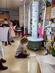 Students in Mrs. Lallensack's first-grade classroom at Monroe Elementary School in Manitowoc surround their classroom grow tower.