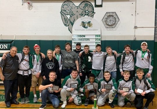 The Madison Rams show off their championship hardware after winning the Tom Ellis Classic wrestling tournament in their gym Saturday. Head coach Bryan Mosier (far back) saw his team score 288 points. Tom Ellis, whose name is on the tournament, is to the far left.