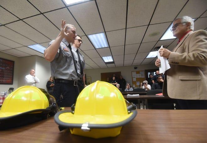 Mayor Tim Theaker swears in new firefighters Luke Adkins and Jared McBride on Monday morning.