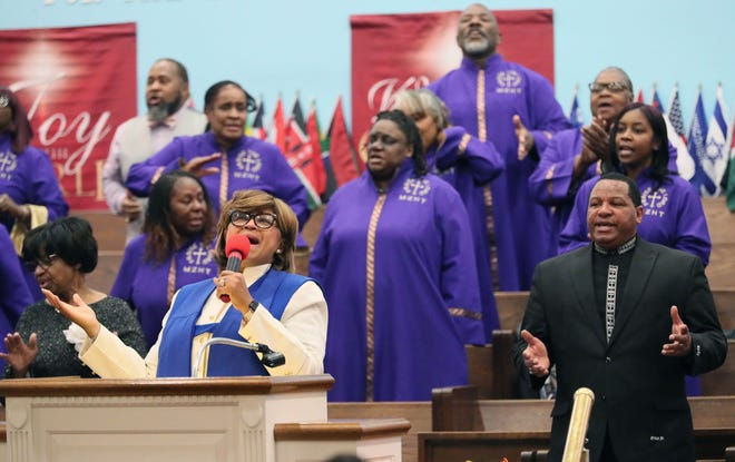 Suffragan Bishop Monica Parchia Price sings along at a service at Mt. Zion Assembly Healing Temple. Her husband, Elder Ricky Price, is at right. The church was founded by her father.