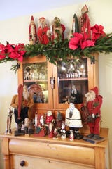 Santa figures made to look like those from the early colonial period grace a wood colonial cupboard made by Beth Jennings' great-great-grandfather, who was born in 1812 and died in 1874.
