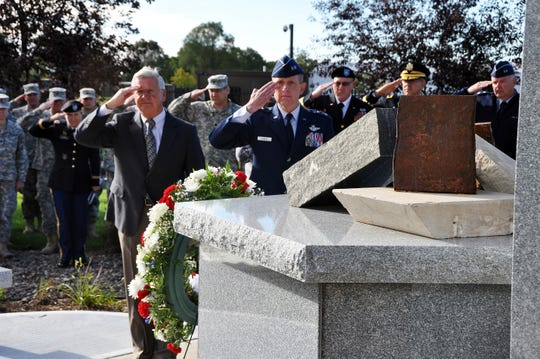 Retired Maj. Gen. Al Wilkening and former Maj. Gen. Don Dunbar salute as Taps is played during a dedication ceremony for a monument commemorating the service and sacrifice of Wisconsin military members since Sept. 11, 2001.