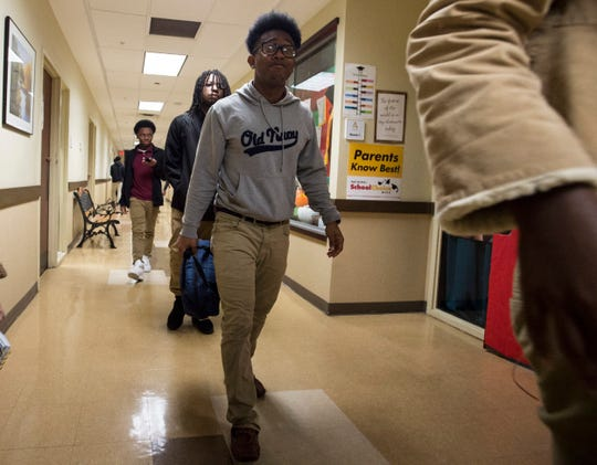 Xavier Johnson walks down the hallway at Accel Day and Evening Academy in Mobile, Ala., on Wednesday, Dec. 4, 2019.