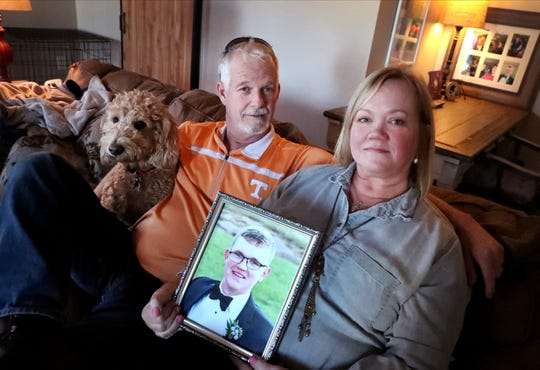 Tammie Elkins holds a photograph of her son, Matthew Cotter, on Thursday, Dec. 5, 2019. Elkins sits with her husband and Cotter's stepfather, Doyle Elkins, and the family dog, Addie. Tammie Elkins got the dog to help cope with her son's death.