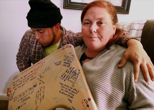 """Kristie Garcia holds a school desk top that was signed by the friends of her son Justin """"Tony"""" Garcia who was shot and killed at their home in La Vergne. Justin's brother Austin Garcia puts his arm around his mom Kristie as he sits next to her."""