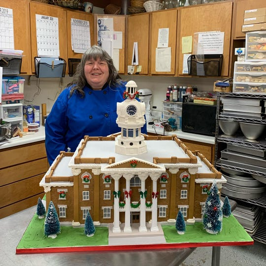 Jo West of Jo's Custom Cakes and Catering in Smyrna stands with a gingerbread replica of the historic Rutherford County Courthouse.