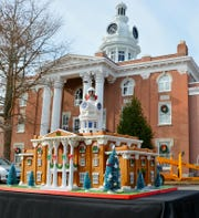 The iconic Rutherford County Courthouse cupola stands tall in the background of a gingerbread house replica built for MTSU by Jo West of Jo's Custom Cakes and Catering in Smyrna.