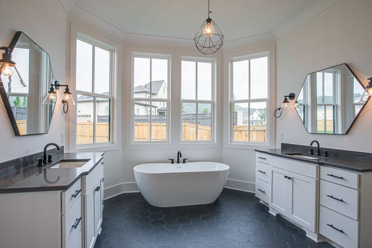 One of the most popular accents to a modern master bathroom is natural light, as seen here via a large bay window. Other trends include unique mirror treatments, vanities with drawers, the freestanding tub and fun accent lighting.