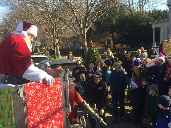 Santa Claus is lowered to the ground by firefighters to greet his young visitors, Dec. 7 in downtown Granville last December. Because of the pandemic, this year Santa will tour Granville by car.