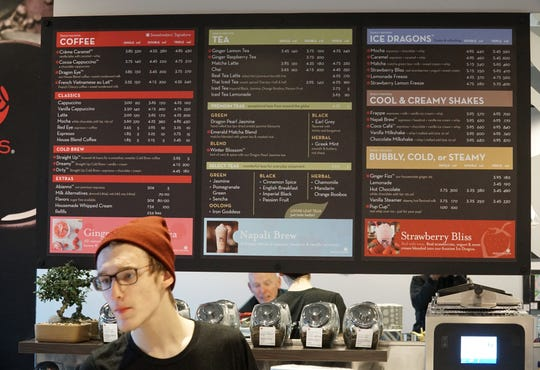 Sweetwaters' employee Zachary Daniel, left, stands behind the Milford coffee shop's counter and in front of its menu board.