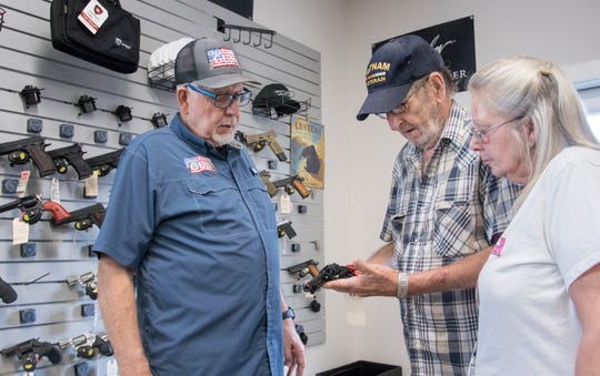 Pete Reeser, left, helps Gaiel and Pamela Noble select a handgun at Gulf Coast Gun in Milton on Monday.
