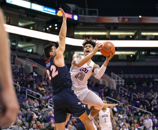 GCU Forward Lorenzo Jenkins (13) goes to the basket against Liberty Flames forward Kyle Rode (22) in the Air Force Reserve Jerry Colangelo Classic on Dec. 8, 2019 at Talking Stick Resort Arena in Phoenix, AZ. (Brady Klain/The Republic)