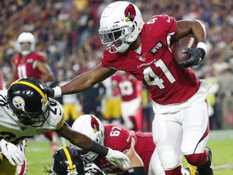 Arizona Cardinals running back Kenyan Drake (41) stiff-arms Pittsburgh Steelers cornerback Mike Hilton (28) during the first quarter at State Farm Stadium December 8, 2019.