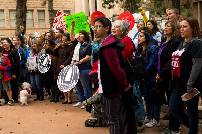 Speakers and attendees are led in a chant at the end of a National Organization for Women rally demanding humane treatment of people, especially women, in immigration detention facilities Sunday, Dec. 8, 2019, at the Arizona Capitol.