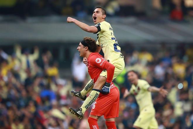 Paul Aguilar y Guillermo Ochoa celebran la victoria del América.