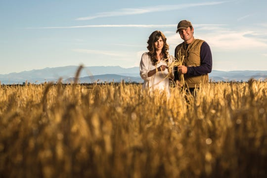Ashley and Colby Frey, owners of Frey Ranch Estate Distillery, take a moment of some of the estate-grown grains used to make their spirits, including a just-released bourbon that is the distillery's first whiskey.