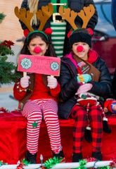 Joslyn Franco, 8, and Ghia Davis, 7, from Girl Scout Troop 215, pose for a photo on their float.