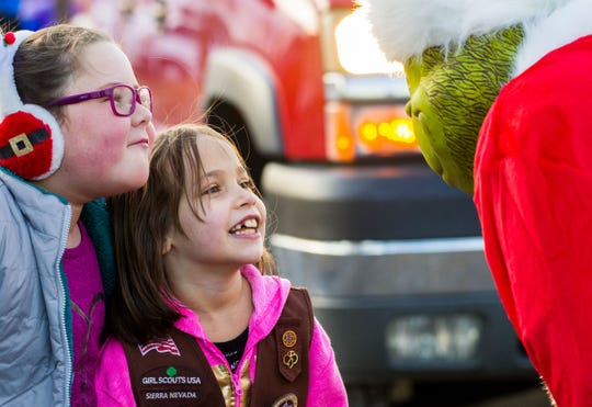 Girls from Scout Troop 215 joke with the Grinch before the parade.