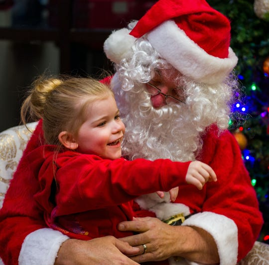 Lily Johnson, 3, enjoys her visit with Santa at City Hall after the parade.
