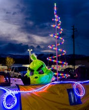 The Grinch waves to the crowd from a float.