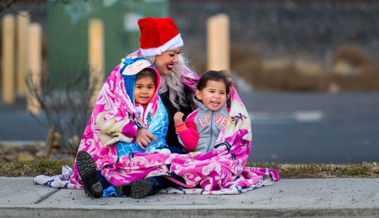 Maria Rodriguez bundles up with daughters Ariana, 2, and Natalia, 4, while waiting for the parade.