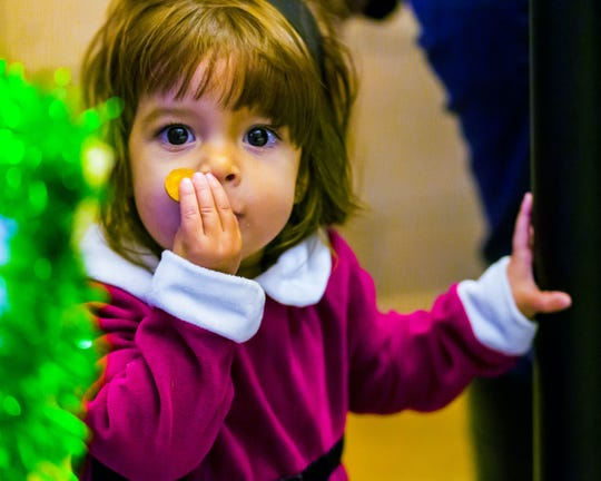 Sarah McCurdy, 1, eats a cookie while waiting in line to visit with Santa at City Hall after the parade.