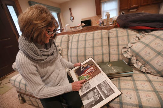 Cathy Behe looks over high school yearbooks, stopping at a photo of her friend Cathleen Schlosser, during an interview in her home in Mount Clemons, Michigan, Wednesday, Dec. 4, 2019.  Cathleen was murdered in Feb. 1982 in Brighton.