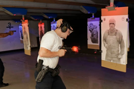 An officer at Washington state's Basic Law Enforcement Academy fires his weapon as a training photo of man not holding a weapon is rotated into view.