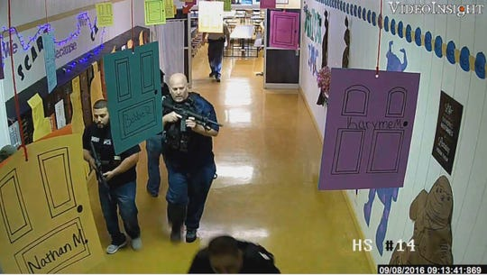 Armed law enforcement officers move through a hallway at Alpine High School in Alpine, Texas, while responding to a shooting at the school. Homeland Security Investigations Special Agent Jon Dangle, center, was wounded during the response after a gun carried by a U.S. Marshal accidentally discharged.