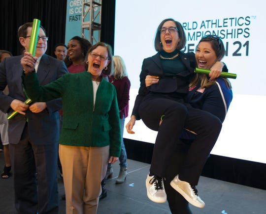 World champion DeAnna Price, right, lifts Oregon Gov. Kate Brown in the air at the end of the kickoff event for Oregon21 at the University of Oregon in October. UO President Micheal Schill, left, and Eugene Mayor Lucy Vinis, center, also attended.