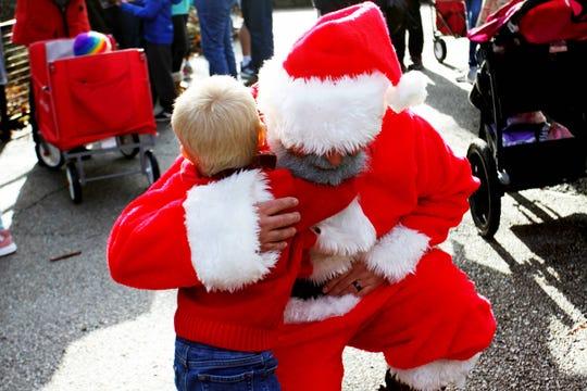 Santa embraces Truman Davenport, 3, at Dickerson Park Zoo Nov. 30, 2019.