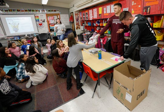Jacob Powelson, second from right, and Zac Sutt, right, members of Evangel University's basketball team, deliver hoodies to Rebekah Mann's third grade class on Monday, Dec. 9, 2019.