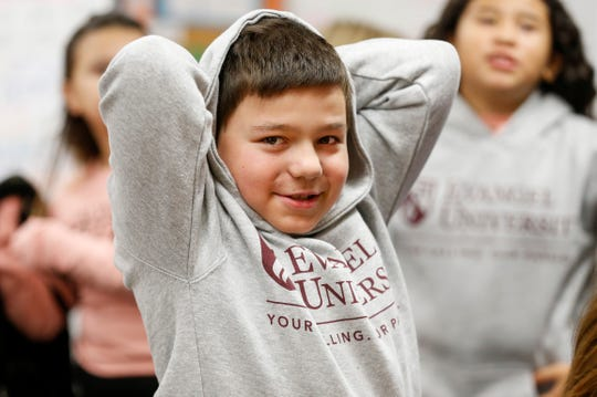 Jesse Flynn, a third grade student at Weller Elementary School, smiles after putting on his new Evangel University hoodie on Monday, Dec. 9, 2019.