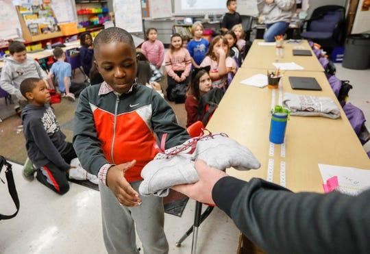 Ansette Karuvante, a third grade student at Weller Elementary School, smiles as he picks up his new Evangel University hoodie on Monday, Dec. 9, 2019.