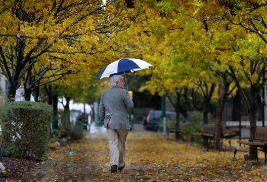 A man walks through San Jacinto Plaza under an umbrella as a steady, all-day rain fell Monday.