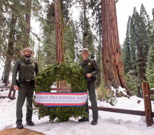 Hundreds gathered Sunday, December 8, 2019 at the General Grant Tree, right, in Kings Canyon National Park to observe the 93rd Annual Trek to the NationÕs Christmas Tree Ceremony. Woody Smeck, Sequoia and Kings Canyon Superintendent, joined two park rangers to place a memorial wreath placed at the base of the 267-foot tree.