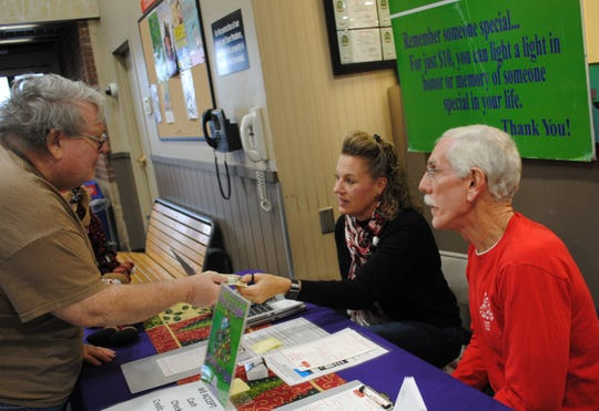 Hospice of Wichita Falls volunteers Brandi Morrison and Larry Schmeltzer receive a donation Monday while at Market Street. Hospice is nearing the end of its annual campaign. This is Morrison's first year to volunteer with Hospice and it is Schmeltzer's third year. Volunteers will be available to take donations to light up the Hospice Tree of Lights through Friday.