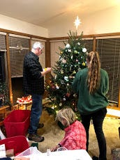 "Steve, Natasha, and Sue decorating our ""store-bought"" Christmas tree."