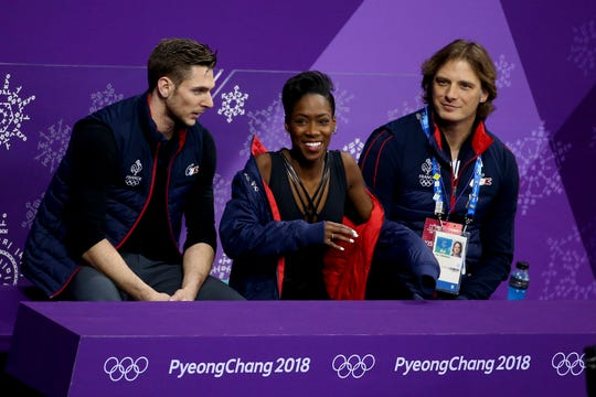 Morgan Cipres, left, is shown with John Zimmerman, far right -- and Cipres' partner, Vanessa James -- after completing the free program at the Olympics in 2018.