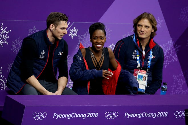 Morgan Cipres, left, is shown with John Zimmeran, far right -- and Cipres' partner, Vanessa James -- after completing the free program at the Olympics in 2018.
