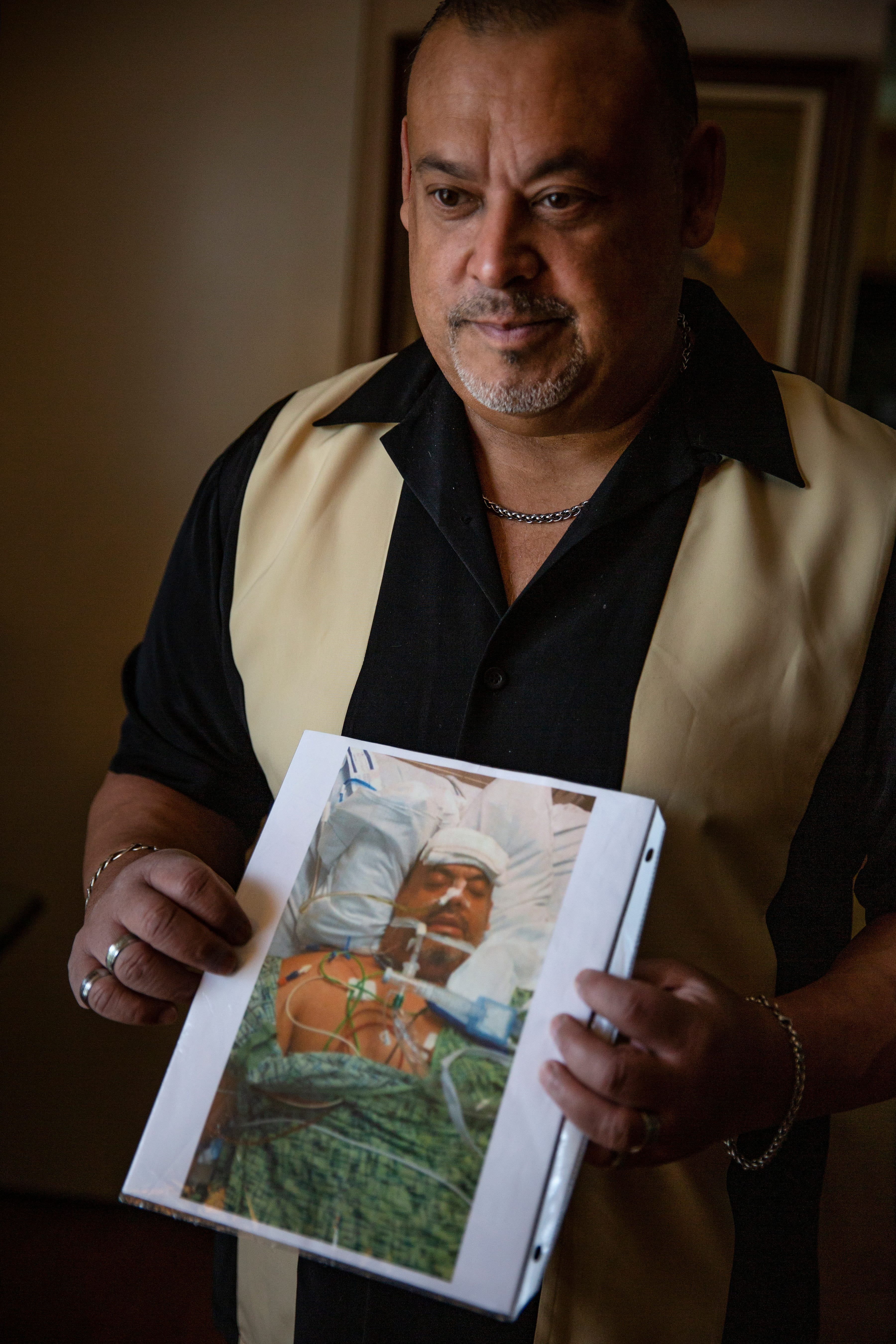 """Ricardo """"Rick"""" Martinez, holds a photo his sister took of him while he was in the hospital recovering from injuries he suffered during a liposuction procedure in 2013."""