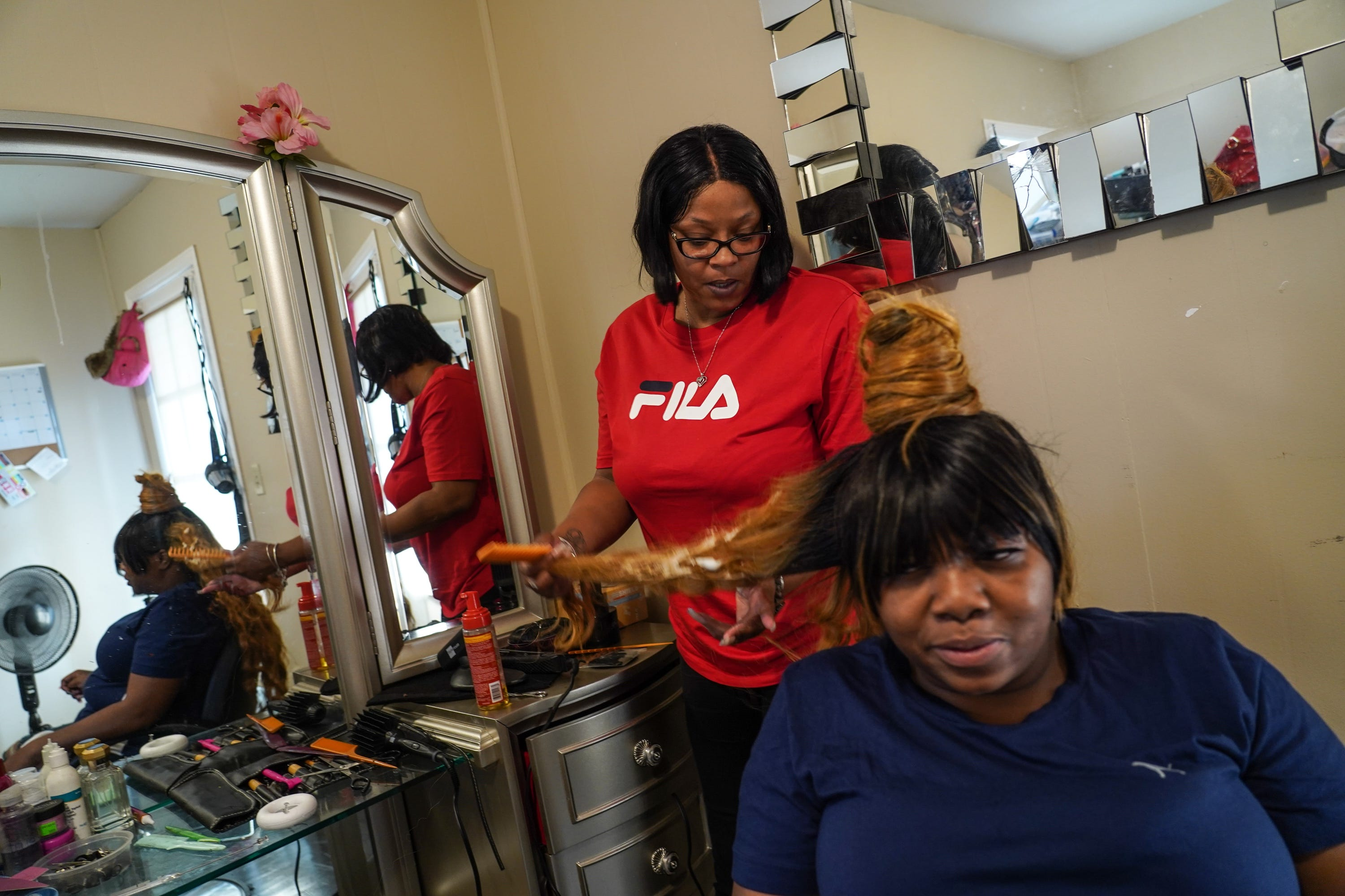 Detroit resident Nyosha Fowler, left, fixes a hairpiece for her friend Tyese White. Fowler lost her job as a truck driver, her apartment and her car after a botched plastic surgery procedure that hospitalized her.