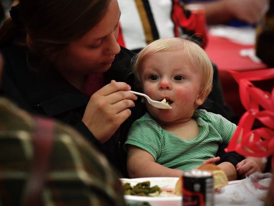 Destane Hennington feeds her son, Braxton Ketscher, 11 months, at Tuesday afternoon at Feast of Sharing, a community dinner at the Abilene Convention Center put on by H-E-B with the help of dozens of volunteers.