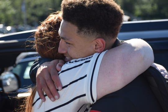 Penney Davis gives her son, Deyondre, a hug after a Junior Olympics track and field meet. Penney raised the four Davis children on her own and is the reason for a kindness they share, says one of Deyondre's coaches.