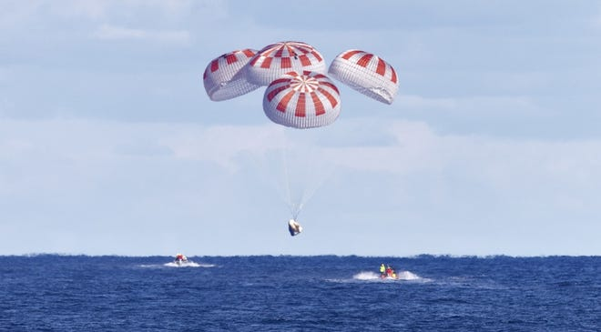 A SpaceX Crew Dragon spacecraft descends under its parachutes at the end of the Demo-1 test flight in March 2018.