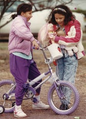 Eight-year-old Brenda Lee steadies her new bicycle while her next-door neighbor, Michelle Chilton, 8, tries to find room for Lee's doll in the basket. They braved chilly weather on Dec. 25, 1990 to try out their new toys from Christmas.