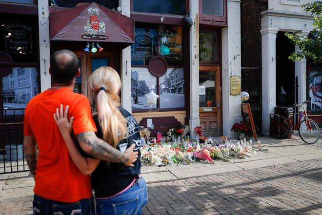 Mourners pause at a makeshift memorial for the slain and injured outside Ned Peppers bar in the Oregon District after a mass shooting that occurred early Sunday morning, Tuesday, Aug. 6, 2019, in Dayton.